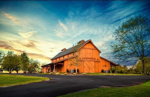 Windy Hill Wedding and Event Barn in front of beautiful sunlit sky with wispy clouds