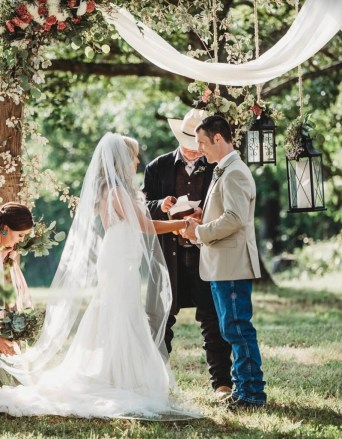 Bride and groom getting married by preacher wearing a cowboy hat