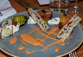 Ed George's tomato salad, burrata cheese, basil, melba toast, tomato vinaigrette.