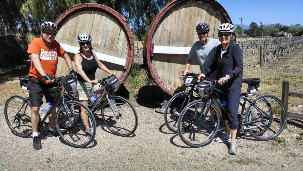 cyclists posing in front of wine casks