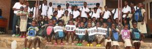 A large group of children dressed in school clothes sit in front of a banner