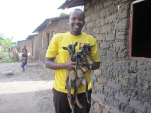 A man holding two goats