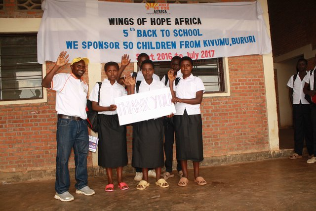 A small group of older children in school clothes hold a thank you sign