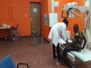 A doctor checks a childs leg while they sit on an operating bed