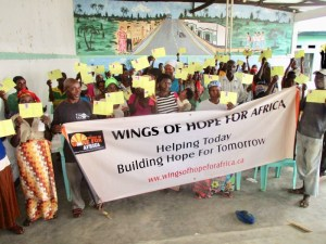 A large group of people holding health care cards and a large Wings of Hope for Africa Banner