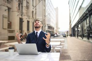 Man in suit frustrated at laptop