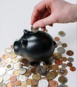 Hand putting money in piggy bank