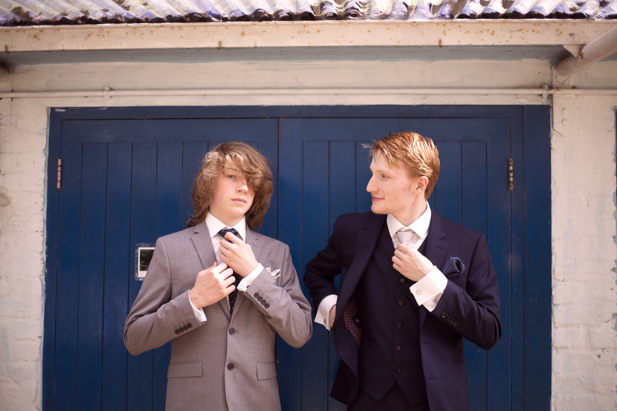 Groom and best man fixing ties at woodland wedding photographer