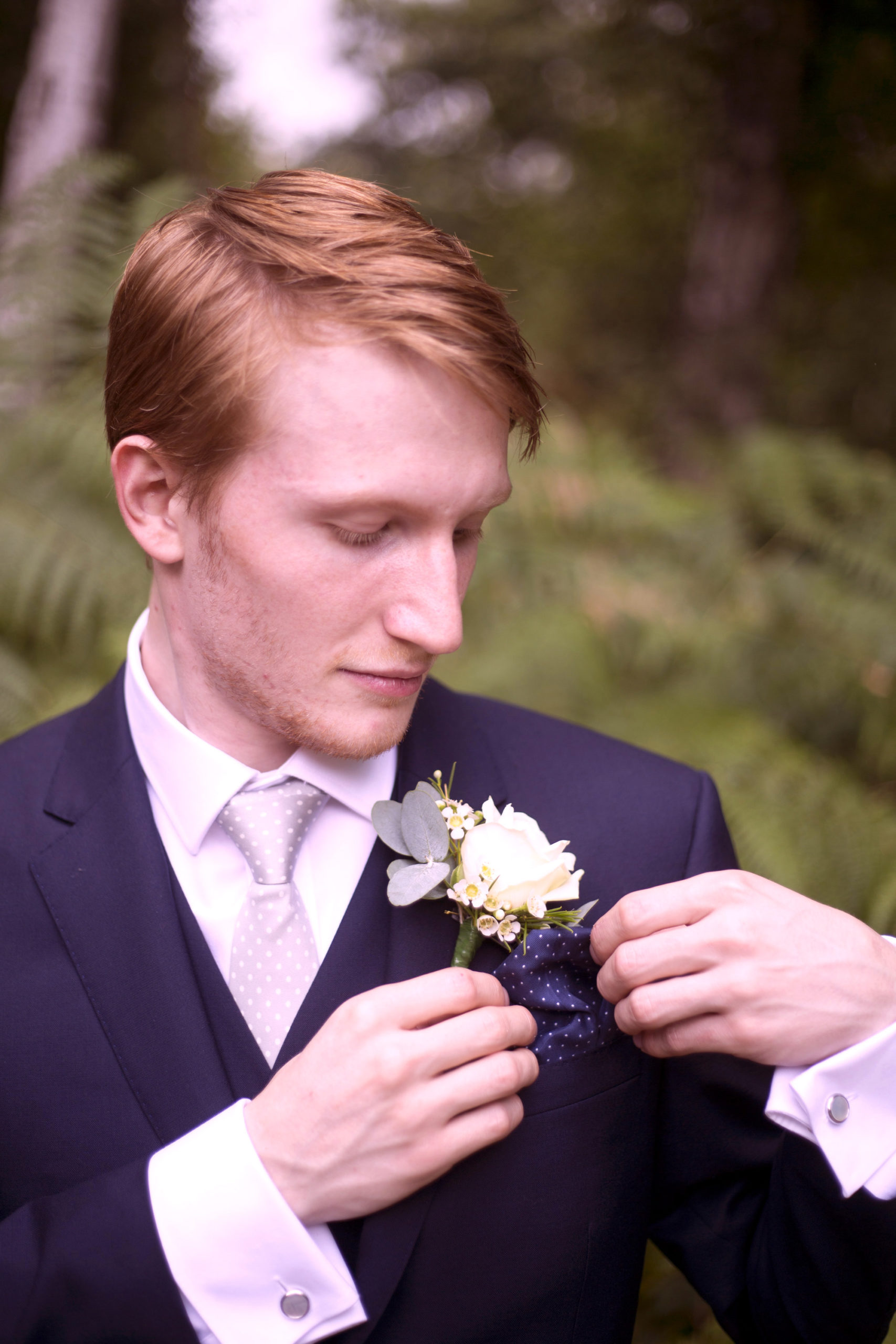 Groom fixing his button hole flower in woodland wedding photographer
