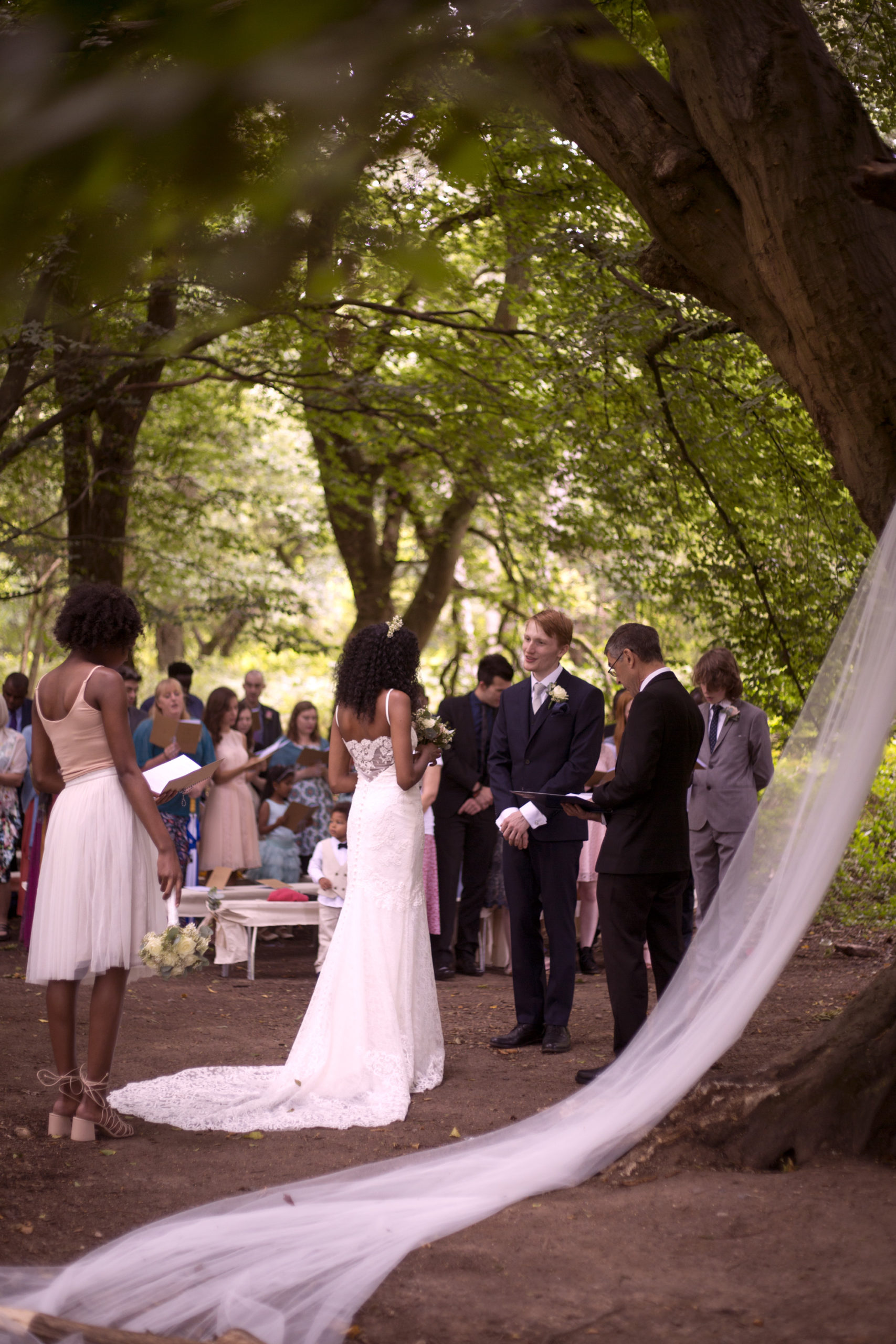 Wedding party stand for outdoor forest wedding ceremony photographer
