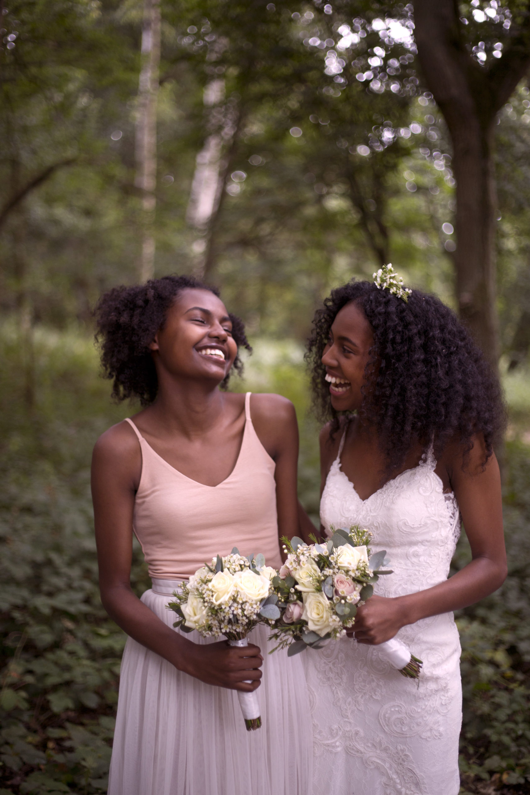 Bride and her bridesmaid laughing during portrait shoot woodland wedding photographer