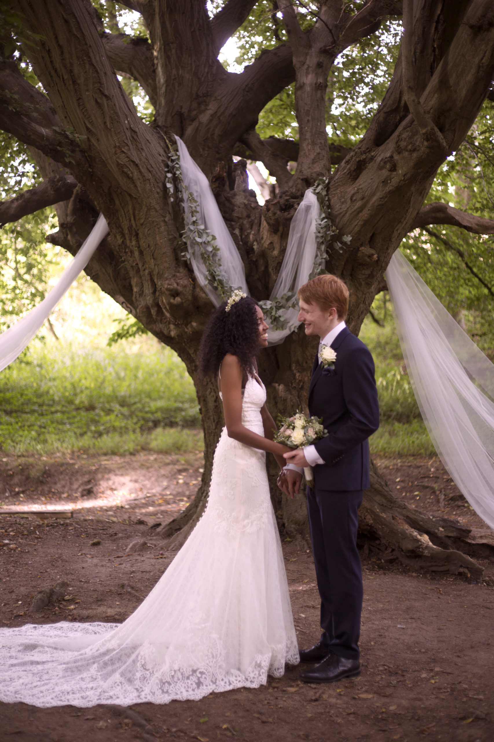 Bride and groom stand in front of the oak tree with hanging organza decorations outdoor woodland wedding photographer