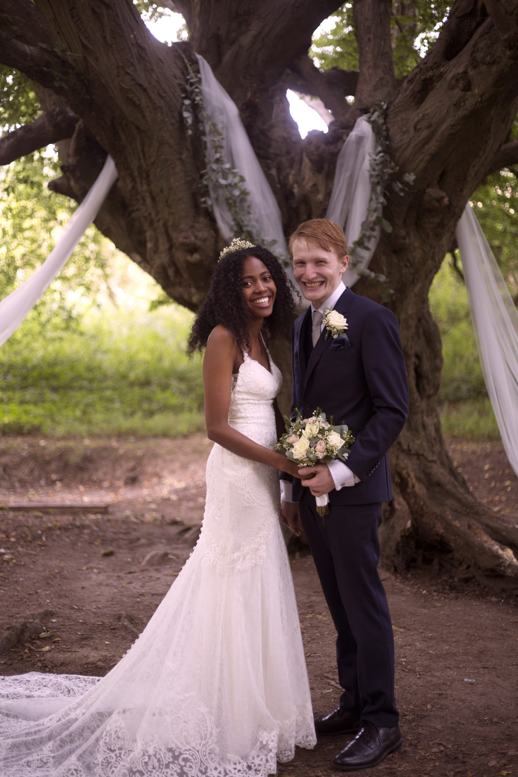 Newlyweds smiling with white rose bouquet Cuffley camp outdoor woodland wedding photographer