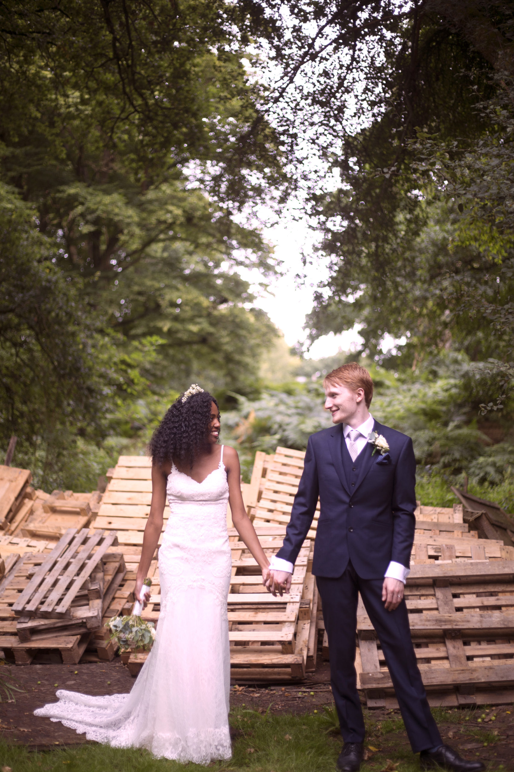 Bride and groom hold hands in front of pallets alternative Cuffley Camp outdoor woodland wedding photographer