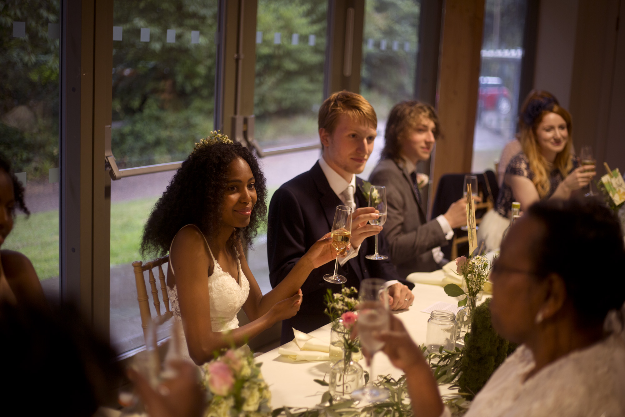 Bride and groom toast at the speeches at Cuffley camp outdoor woodland wedding photographer