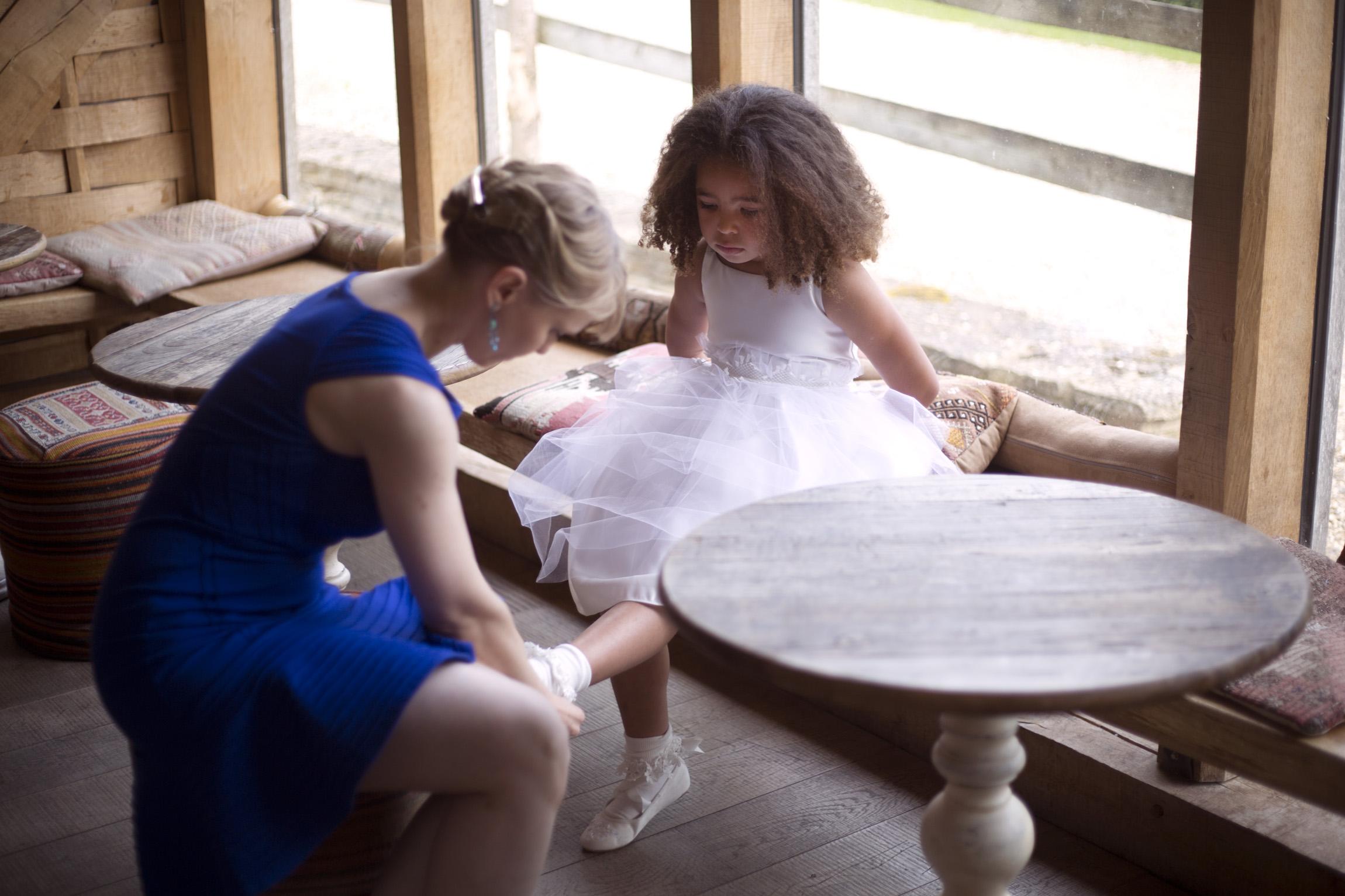 Wedding guest helping flower girl put on her shoes Cripps barn outdoor wedding photographer