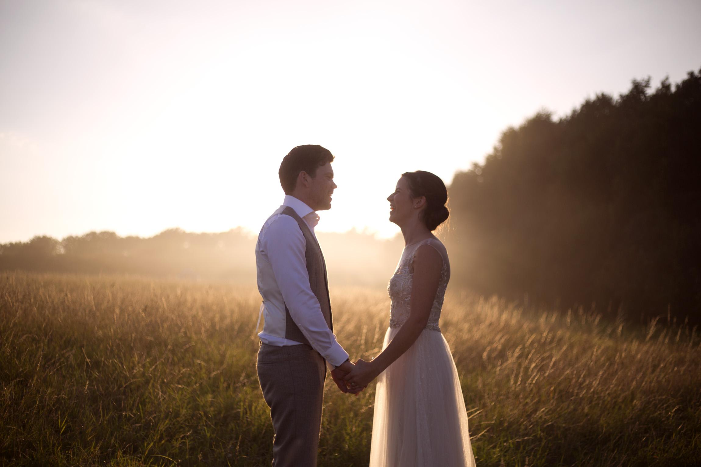Couple laughing sunset golden hour sun flare Cripps barn outdoor wedding photographer