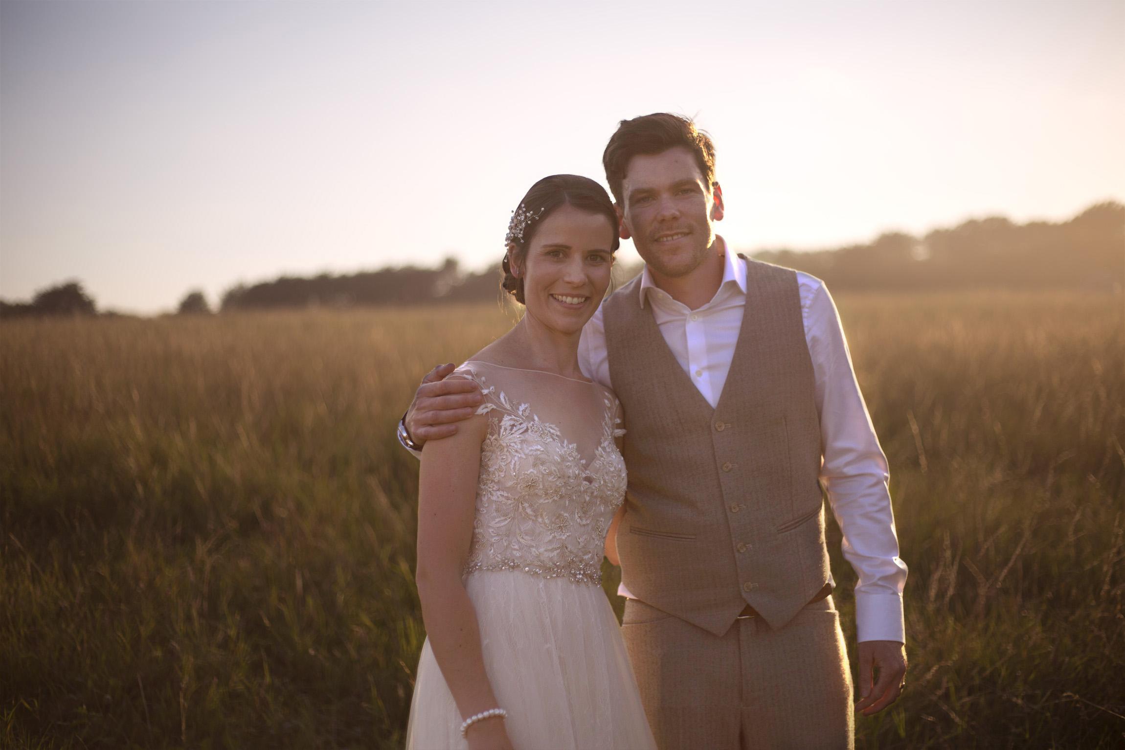 Newlyweds smiling sunset golden hour field Cripps barn outdoor wedding photographer