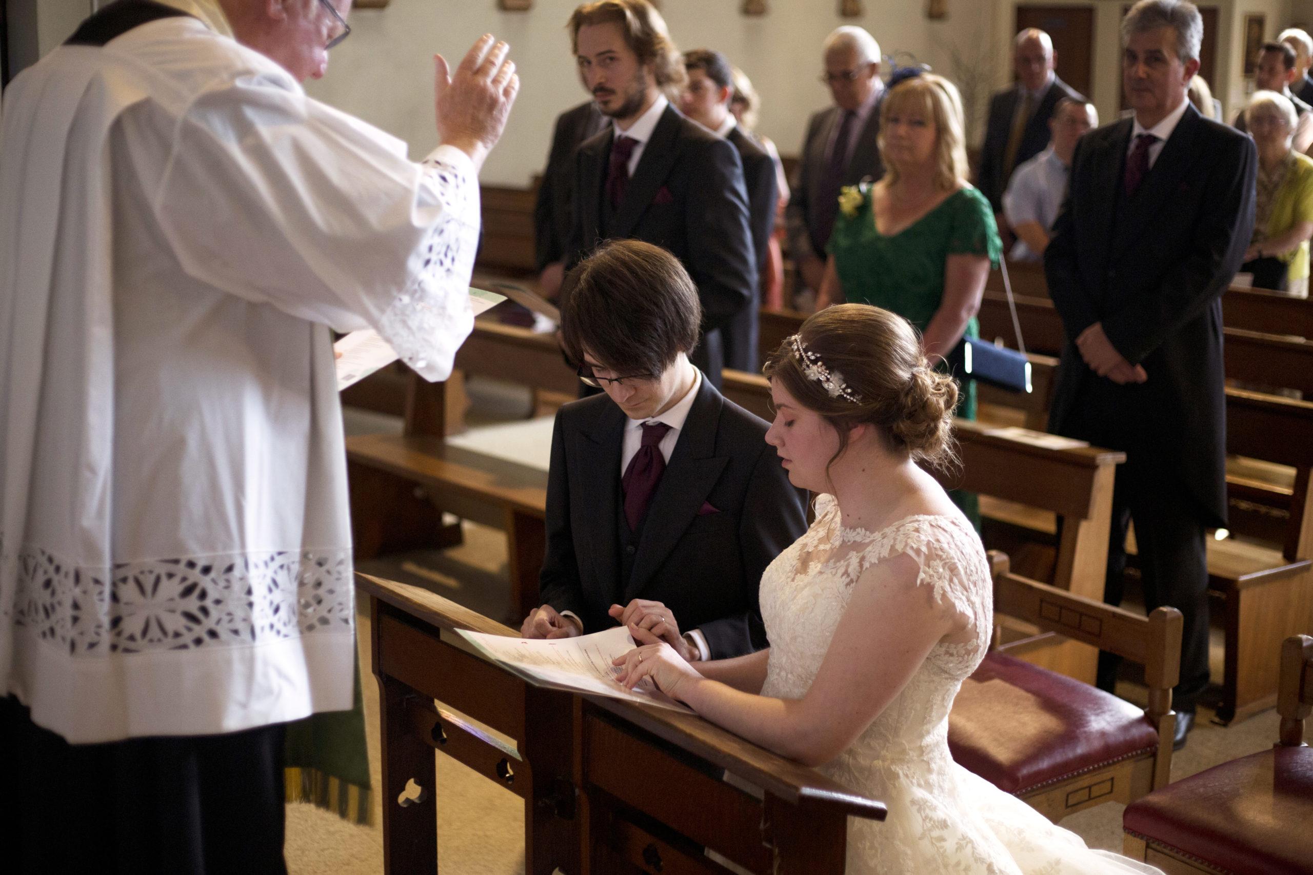 Bride and Groom kneeling for prayer blessing Wedding photographer Cardiff St Teilos Church