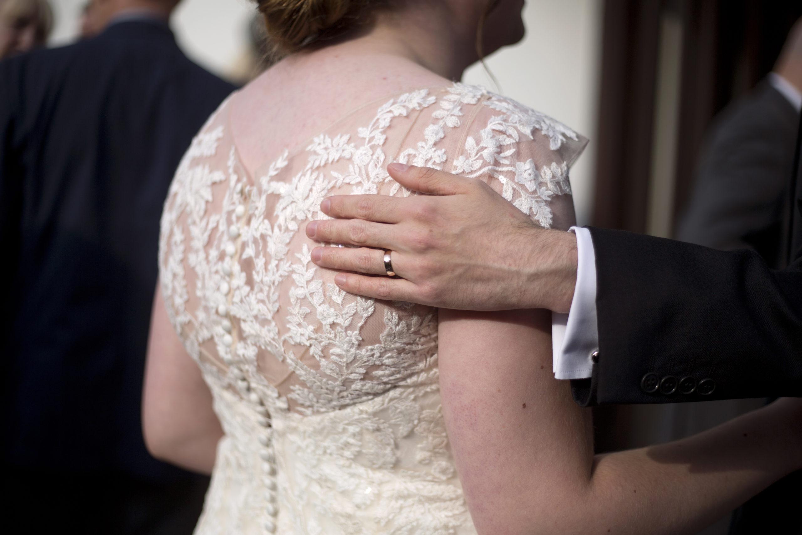 Groom's hand on bride's back lace wedding dress Wedding Photographer St Teilos