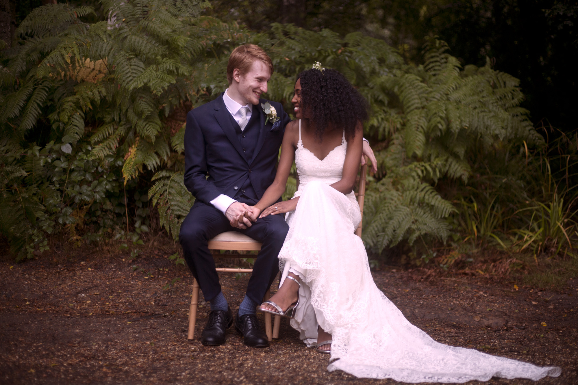 Bride and groom sit for their portrait after the ceremony with fern background outdoor wedding photogapher