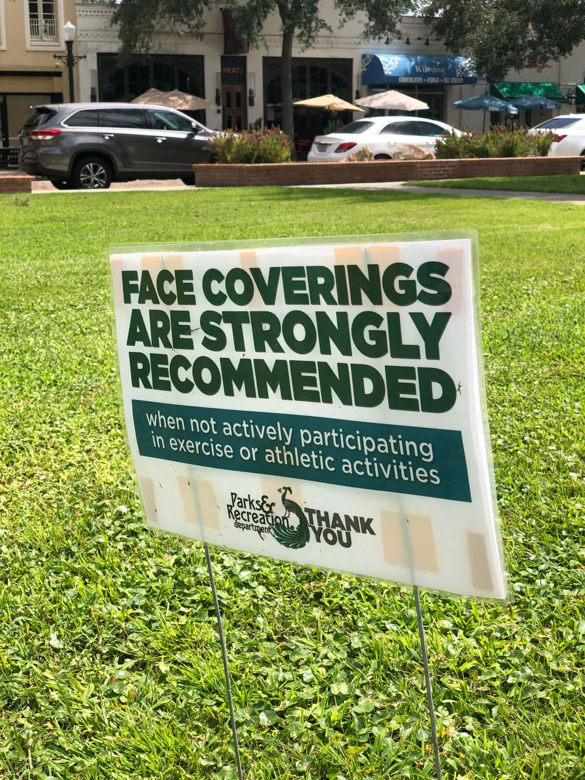 Face Covering Recommended sign in Central Park in WInter Park Florida