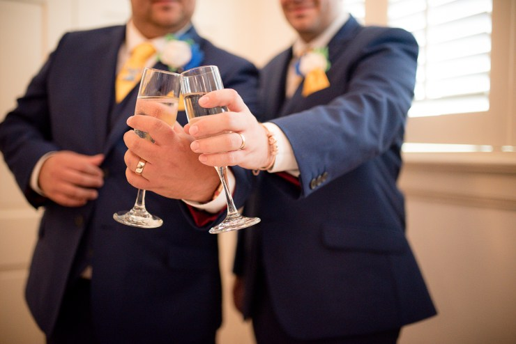 Same sex couple clink their glasses and show off their wedding rings