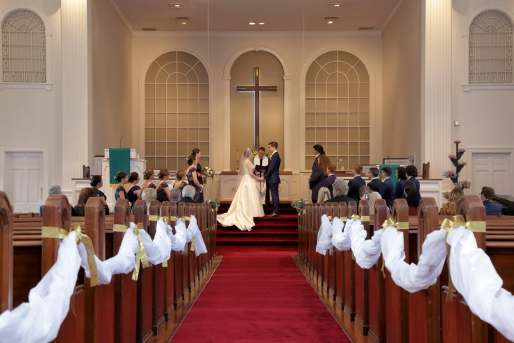 A long shot down the aisle of the First Congregational Church in Winter Park which is decorated either side with flowing white fabric and the couple is in the distance getting married while the wedding guests look on.