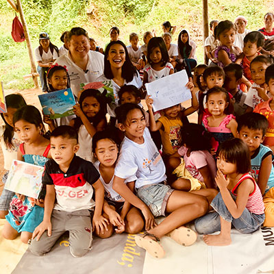 Dean Russell reading his children's books to children in the Philippines jungle