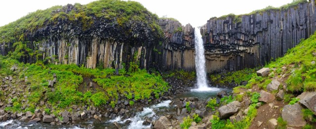 svartifoss waterfall. Wide basalt cliffs with a narrow, powerful waterfall.