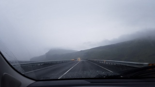 Driving in Iceland - two lane road with oncoming car with headlights on, overcast sky, steep mountains in the distance.