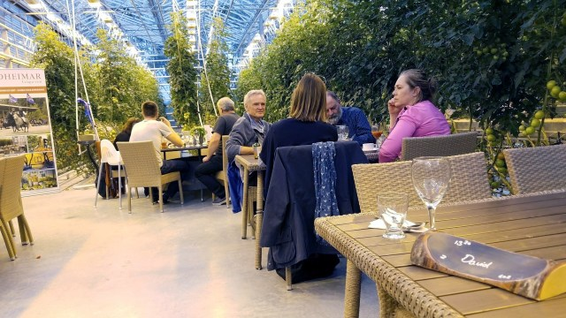 Greenhouse with restaurant tables and patrons inside it.