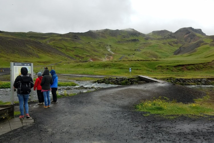 Geothermal valley with hikers on a path, green hills and steam coming from small vents