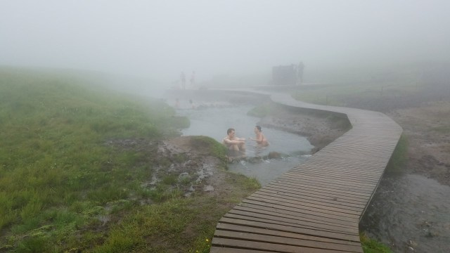 Geothermal river with boardwalk crossing the water, people sitting in the river and a wooden windbreak in the mist.