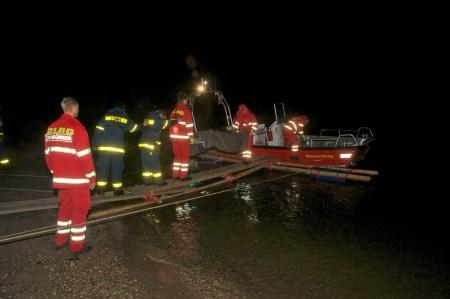 Zwei THW-Helfer führen den rückwärts gehenden Träger der Trage, damit diese mit seiner Last nicht daneben tritt. (Foto: Andreas Lerg)