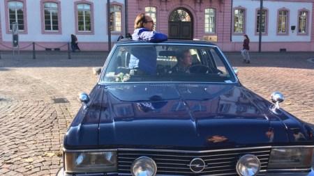 """SWR Fernsehen AB DURCH DIE HEIMAT (3), """"4 Comedians unterwegs im Südwesten - Mainz"""", am Dienstag (05.04.16) um 21:00 Uhr. Lars Reichow und Christoph Sonntag (li.) unterwegs in Mainz mit einem Opel Admiral. Hier am Schillerplatz vor dem Bassenheimer Hof mit Blick auf den Fastnachtsbrunnen. © SWR/Bavaria/Max Serges"""