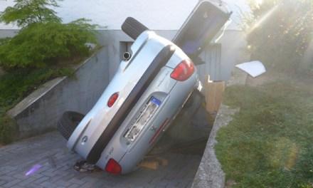 PKW landet bei Unfall auf der Seite in einer Garageneinfahrt