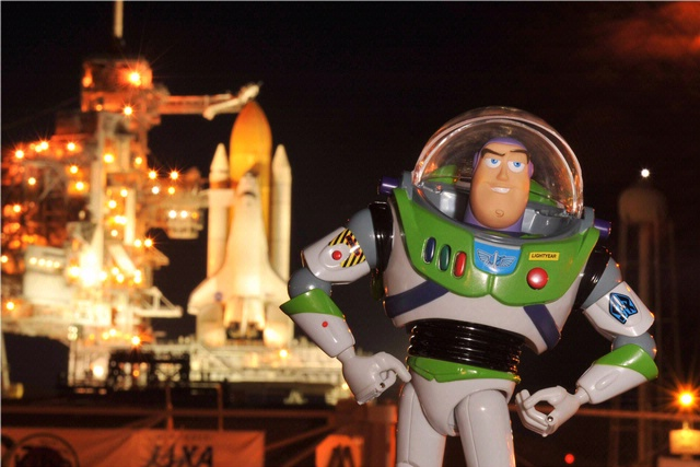 Buzz Lightyear toy posing in front of space shuttle in 2008. Image Credit: NASA