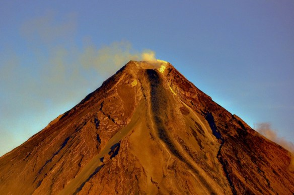 The conical summit of Mayon in the Philippines. Paths of previous lava flows and pyroclastic flows can be seen on the steep slopes of the volcano.