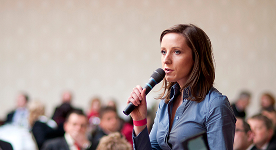 women speaks to an audience