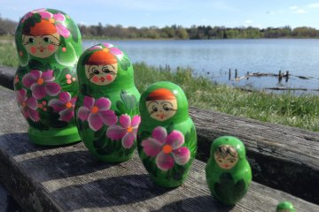 Row of nesting dolls by lake.