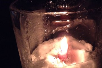 Candle glowing inside ice.