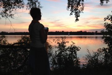 woman standing by lake at sunset