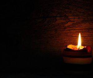 single candle shining in the dark.