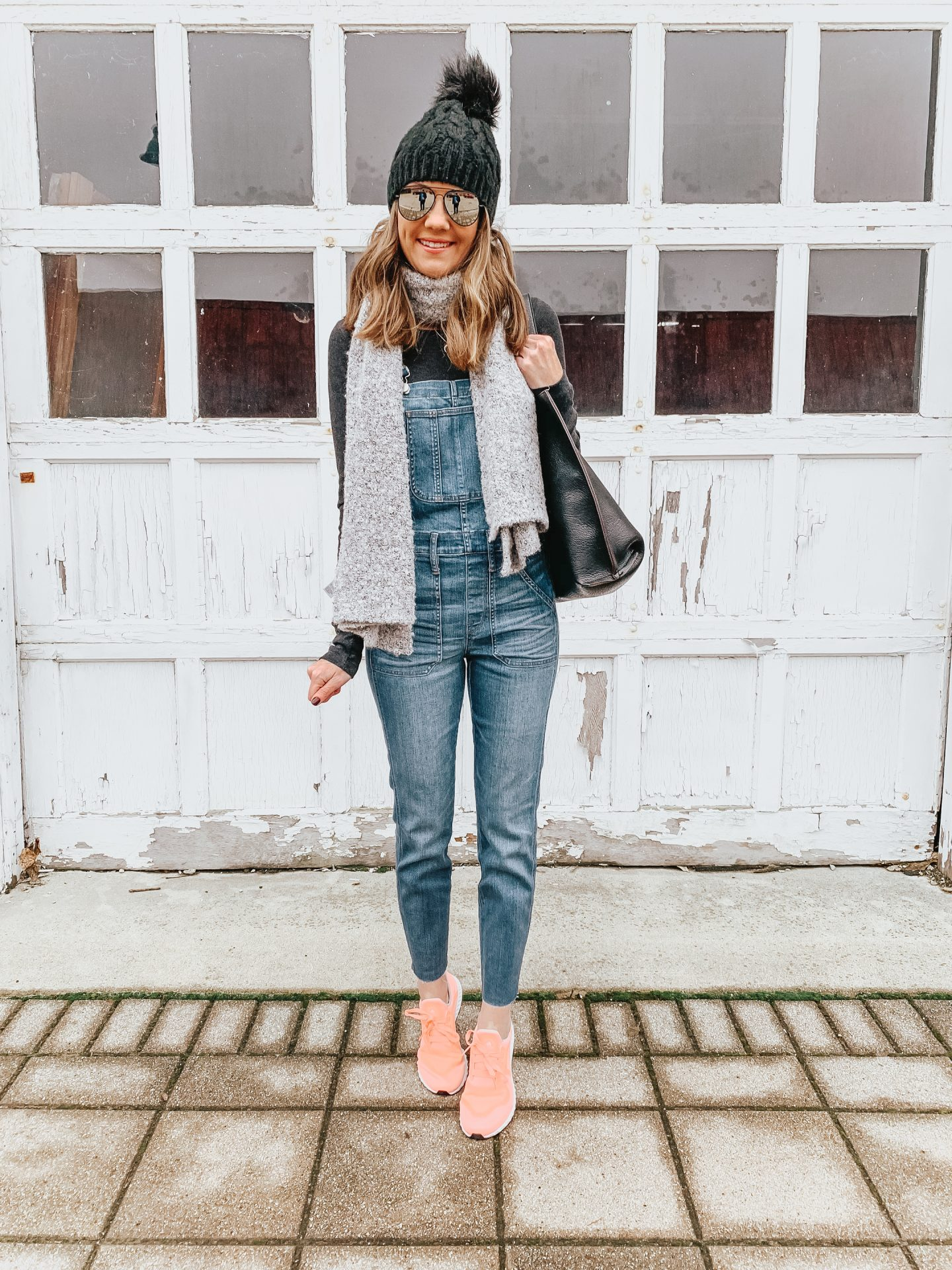 how to style overalls in the winter, Madewell skinny overalls, black plaid scarf, pink Adidas sneakers, overalls over age 40