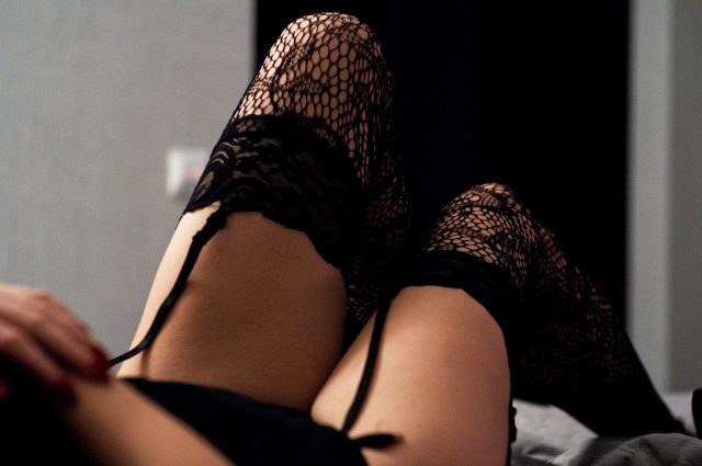 White femme legs in fishnets that art attached by a garter belt. There is a grey wall in the distance behind them as they lay in bed.