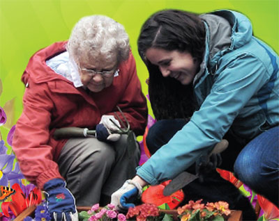 Elderly woman and daughter planting flowers