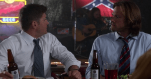 Dean looking in opposite direction with Sam staring angrily at him