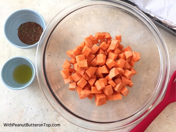 Easy Roasted Sweet Potato Bites - a simple, crispy and flavorful side to your next dinner or even the perfect salad topper that you won't be able to stop eating! #sweetpotato #baked #bites | https://withpeanutbutterontop.com