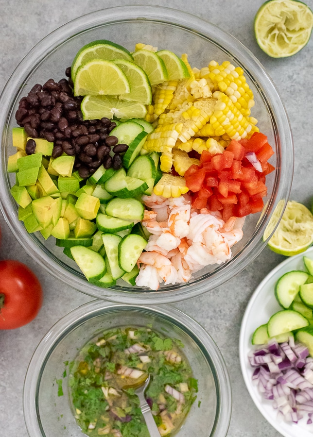 Clear mixing bowl filled with avocado, black beans, limes, diced tomatoes, shrimp, cucumbers, and corn.